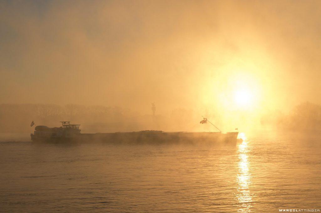 Binnenschip op de Waal bij Tiel vaart de zonsopgang in de mist tegemoet