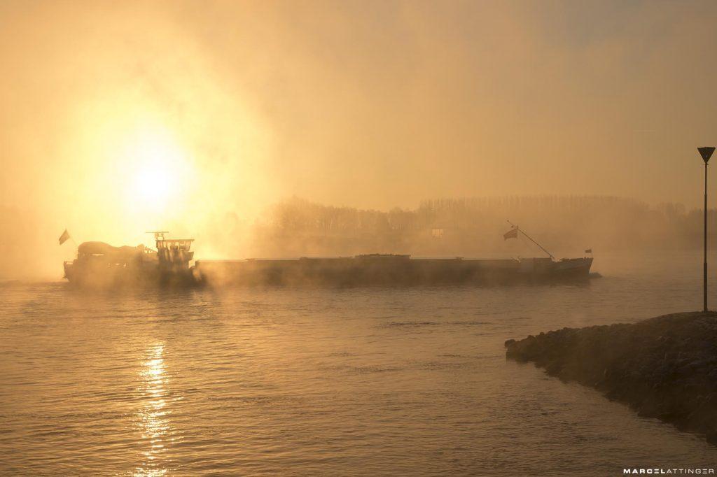 Schip op de Waal tijdens zonsopgang in de mist